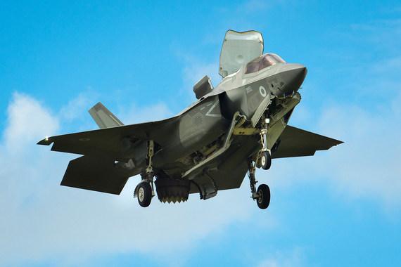 F-35B, самолет укороченного взлета и вертикальной посадки ВВС Великобритании, в режиме висения. На фото видно отклоненное вертикально вниз сопло двигателя F135-PW-600, а также открытый верхний люк и нижние створки расположенного за кабиной подъемного вентилятора. Укороченный взлет позволяет истребителю базироваться на кораблях, не оснащенных катапультой