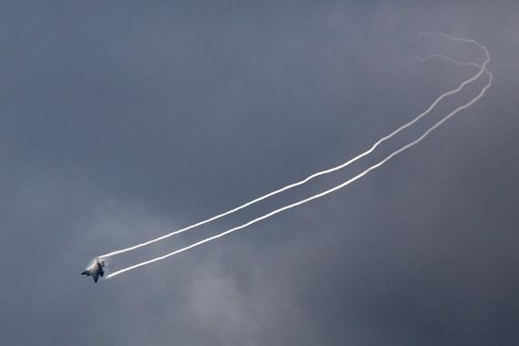 F-35 выполняет вираж над Фарнборо. В контрастном свете различимы концевые вихри и конденсация влаги в области пониженного давления над крылом