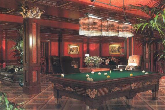 Гостиная с бильярдом расположена на цокольном этаже, рядом с ней - домашний кинозал, курительная с баром, винная комната, три гардеробные и оружейная