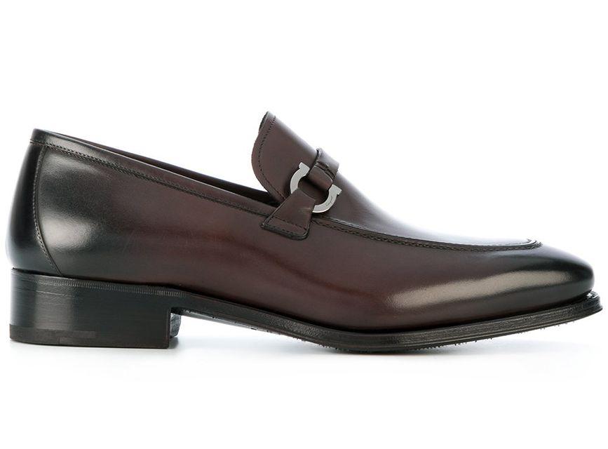 Salvatore Ferragamo предлагают более строгую модель лоферов темно-коричневого оттенка с U-образной пряжкой к деловому стилю.