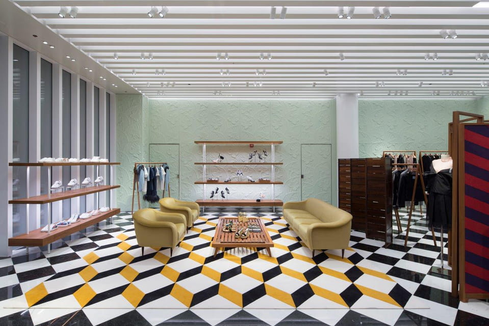 Многое в оформлении бутика отсылает к классической концепции магазинов Prada, например, «шахматный» пол из мраморных плит