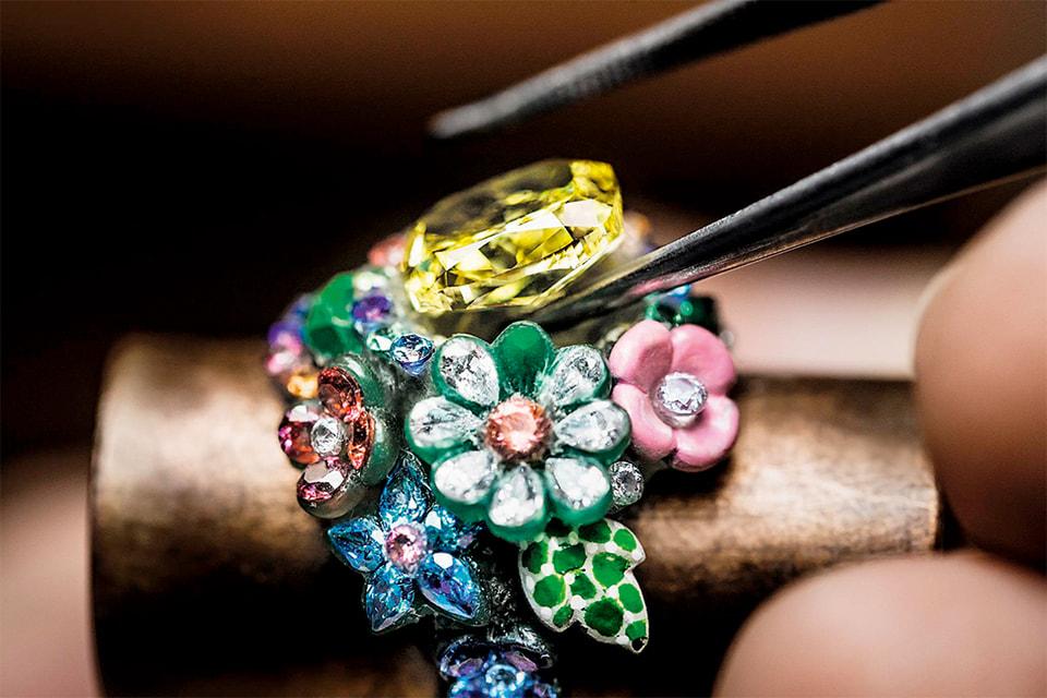 Посередине букета цветов в кольце Hameau De La Reine красуется желтый бриллиант