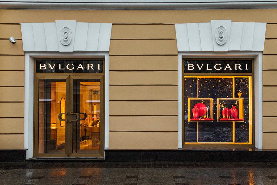 Сияние витрины на первом этаже элегантного исторического здания поддерживает фейерверк праздничных огней Невского проспекта