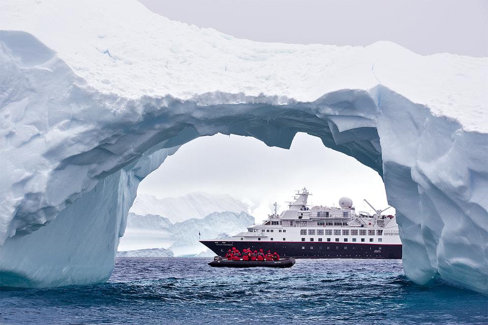 Участники одного из круизов Silversea фотографируют айсберги с борта надувной лодки
