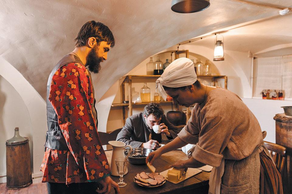 Сцена из спектакля «1898» на кухне; героиня спектакля обучает зрителей правилам столового этикета XIX века