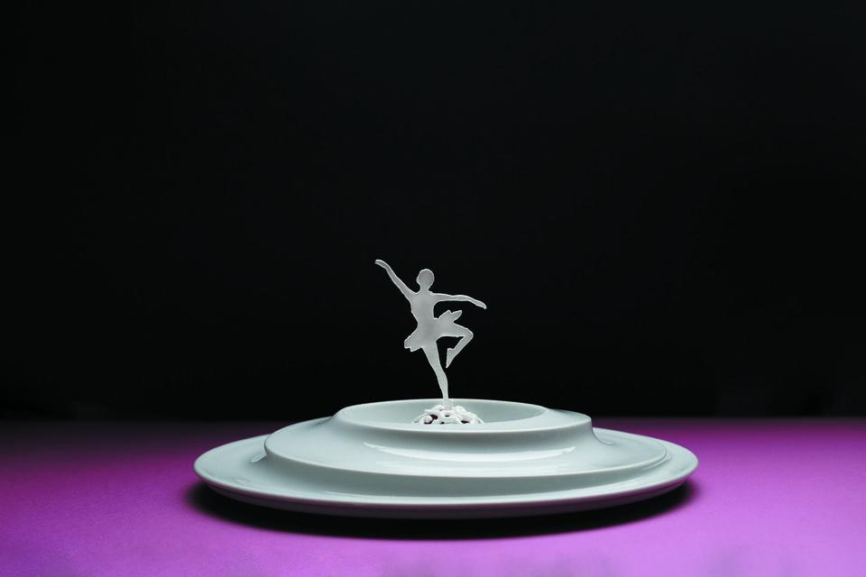 Балерина стоит на одной ноге и вращается вместе с тарелкой