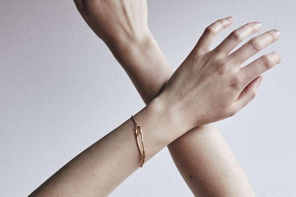 Браслет из розового золота в виде стилизованной английской булавки на цепочке можно непринужденно носить каждый день