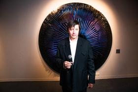 Автор выставки Василий Клюкин на фоне одной из своих работ